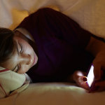 Teen texting at night in bed